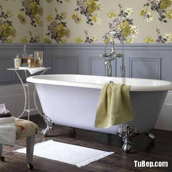 Bathroom, grey wood panelled wall and Designers Guild large print floral wallpaper, freestanding roll top bath with mixer taps and shower CH&I 03/2010 pub orig