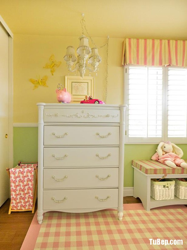 A tall dressser with a chandelier with decorative crystals, checkered rug, storage bench fill this little girls room with design and color.