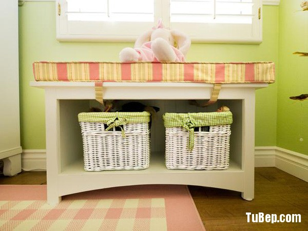 Girls bedroom storage bench with wicker baskets for storing kids toys and items and a seating area with stuffed animal. This area has a pink checkered rug on the floor under the window.