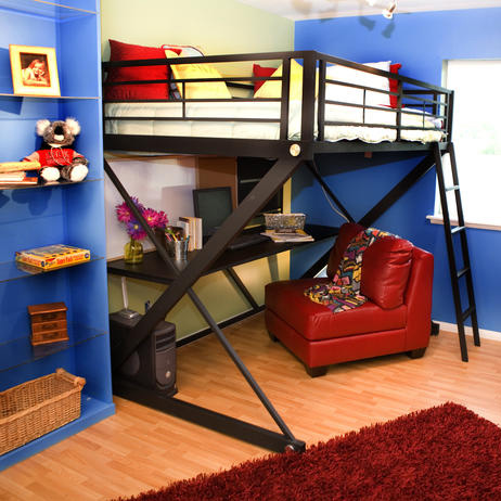 This child's bedroom gets a red and blue color scheme by designer Tori on this challenge of Design Star on HGTV. A red chair with a computer desk sits under the bunk bed, with shelving, and an art easle to the side.